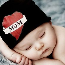 """Sew up a simple newborn hat from black knit. Embellish with red heart, white ribbon and the word """"mom."""""""