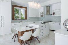 un îlot central et blanc dans la cuisine moderne et blanche