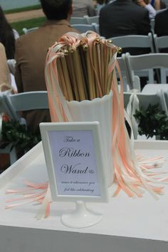 Home made peach, ivory, and gold ribbon wands used during the ceremony. Sign is a photo frame from Ikea.