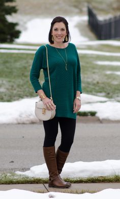 How to Wear Brown Boots with Black Based Outfits: Brown Riding Boots with Black Leggings and a Tunic Sweater in a rich Jewel Tone