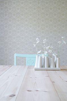 köksbord : low-contrast wallpaper, (birch?) light wood tabletop, accent colour chair, white decorative pieces.