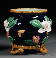 George Jones Majolica Jardiniere, England, late 19th century, decorated with flowering branches and moths to body, branches extend from flowers around base and form the three feet, pad mark, ht. 10 1/2 in.