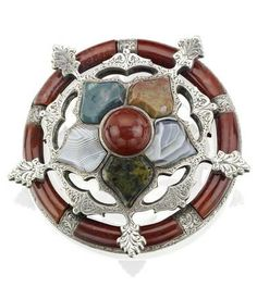 A Victorian Scottish agate brooch Of stylised snowflake design, set with vari-cut, vari-coloured agates, the mount with scrolling engraving, to a circular frame inlaid with reddish agates, inscribed to the back 'To my God-Daughter Rosamond', mounted in silver, width 54mm, together with a part bracelet formed as a series of four vari-coloured domed faceted agate plaque.