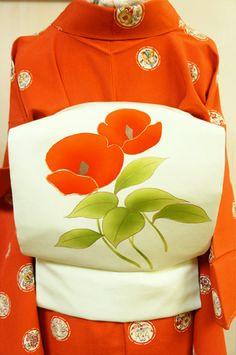 ごく淡いバウダーがかった澄んだ爽やかなグリーンの地に、モダンにアレンジされた椿のようなお花模様が凛と美しく染め出された正絹塩瀬の名古屋帯です。