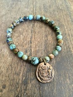 This beautiful bracelet is beaded with gorgeous African Turquoise gemstone and detailed bronze beads featuring an artisan mermaid.