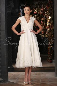 Wedding Dress by SimplyBridal. With a classic silhouette and clean lines, this satin tea-length gown is a fantastic choice for casual outdoor weddings and brides with a fuss-free style. It can be dressed up to fit a variety of vintage and formal themes. The V-neck accents the bust with. USD $369.99