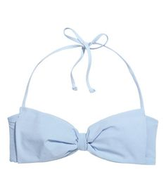 Lined bikini top with lightly padded cups. Large bow at front. Boning at sides, detachable ties at back of neck, and metal fastener at back.