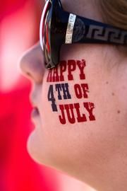 """Lauren Blair, 11, of Belton, Texas, shows her patriotism while watching the Belton July 4th Parade held annually since the mid 1800s. In 2008 USA Today named the Belton 4th of July Parade as one the nation's """"Top Ten Places to Fly Your Flag on the 4th."""""""