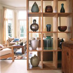 Wooden shelves divide this room, letting in light and displaying vases in the same shades as the cushions and rug.