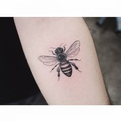 Bee tattoo on the left inner forearm.