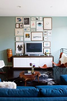 Eclectic Living Room with Albion burl slice table, Cow hide rug, Gallery wall, Cynthia left-facing sectional, navy