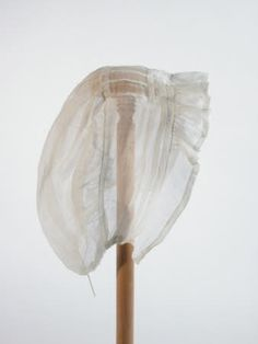 Cap - 1810     White muslin coarse weave. Helmet style, with fuller part at back of head, gathered at back by cord. Two tucks and frill on front. 1810 (circa)