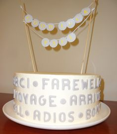 Going Away Cake...  Vanilla Italian meringue buttercream decorated in fondant letters...farewell; adios; bon voyage; arrivederci.  Topped with handmade banner.