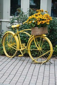 Gartendekoration mit einem gelben Fahrrad