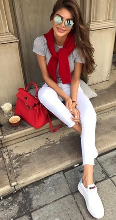 A quick way to sprinkle some preppy charm onto your outfit? Tie a bold red sweater around your shoulders. Keep the rest of your colors crisp and monotone, not forgetting brilliant white sneakers for an athleisure twist.