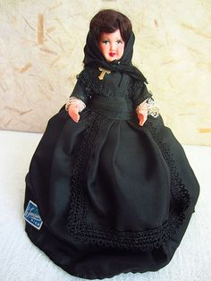 This little lady is rather small, but highly vintage, made of celluloid, dating from the fifties. She is a Corsican, a lady from the island of Corsica (Corse).  Typically, a Corsican doll will mostly wear black, especially a large black scarf, worn over the head and tied tightly under the chin and wear a prominent cross, which is the case with this lady, who is entirely garbed in black, adorned only by black and white lace on her dress, shawl and apron. She also wears a starched white simple…