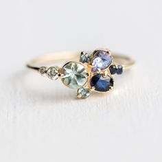 The Clear Water Ring features a cluster of aquamarine, teal & dark blue sapphires, tanzanite & tiny diamonds in an asymmetrical design that is prong set in 14k gold.