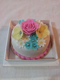Mini Bolo decorado com pasta americana e lindas flores! Para encomendas personalizadas acesse o link www.lejonconfeitaria.com.br