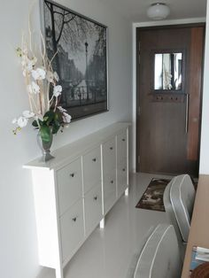 flowers in a vase, placed on a narrow white cupboard with eight compartments, hallway furniture ideas, near a brown front door, and large framed photograph Living Room Storage, Hallway Furniture, Furniture, Brown Front Doors, Interior, White Cupboards, Home Decor, Ikea Hack Living Room, Small Hallway Decorating