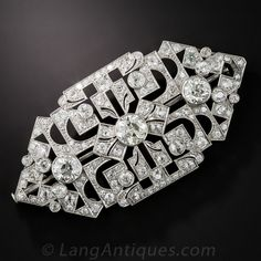 The three principal old mine-cut diamonds alone weigh over 3.50 carats in this opulent Art Deco brooch, hand crafted in platinum, circa 1925. The elaborate geometric pattern with its open architecture allows the fabric on which the pin is worn to create a back-drop which further emphasizes the stunning beauty and intense sparkle of this impressive piece. An additional 5.20 carats of smaller old mine-cut diamonds bring the total diamond weight to just shy of 9 carats. Sizable: 2 1/2 by 1 1/4…