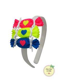 Arco revestido com viés de cetim, decorado com 3 bombons de feltro em cores fosforescentes.