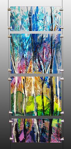 This four piece fused glass panel of a colorful sun-drenched forest clearing in a somewhat abstract depiction is hung vertically from a floor to ceiling cable that grips each glass panel.