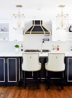 A Dated Kitchen Gets a Stunning Modern Makeover// traditional bar stools, glamorous kitchen, black and brass hood, black kitchen isalnd