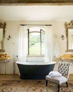 A vintage slipper chair in the master bath is upholstered in a Dedar linen, the tub fittings are by Lefroy Brooks, and the Spanish silver-gilt mirrors and antique Khotan rug were purchased at Christie's.
