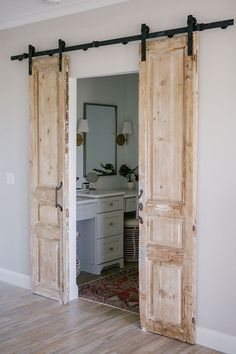 Hung on barn door hardware, these antique doors add personality and architectura. Hung on barn door hardware, these antique doors add personality and architectural interest to this bathroom Barn Door Pantry, Bathroom Barn Door, Double Barn Doors, Antique Doors, Vintage Doors, Coastal Farmhouse, Farmhouse Homes, Farmhouse Style, Farmhouse Bedrooms