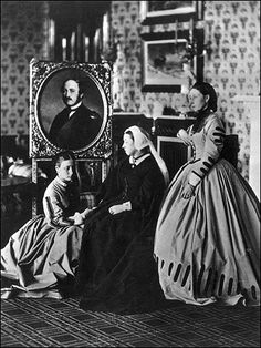 Princess Louise, left, with mother Queen Victoria and sister Princess Alice, 1863. Another mourning photograph for Prince Albert - his gilt-framed portrait stands behind Louise.