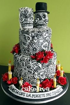 bride and groom skulls make the third layer in a black and white detailed cake with red roses on it