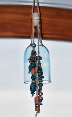 wine bottle wind chime - after you turn the bottoms into candleholders or glasses, use the tops to make windchimes!