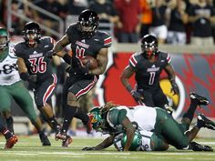 University of Louisville's Corvin Lamb (4) breaks free from University of Miami's Nantambu-Akill Fentress (28) as he runs the kick-off back for the touchdown during the first half of play at Papa John's Cardinal Stadium in Louisville, Kentucky.       September 1, 2014