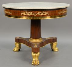 Rosewood Gueridon having round marble top over brass inlaid frieze mounted with gilt bronze set on gilt bronze mounted plain shaft with gilt carved paw feet. Realized Price $5,100.00