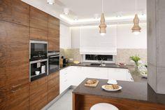 W kuchni ważną rolę pełni drewno na meblach. Jego urok podkreśla naturalne światło, które wpada tu przez duże okna. Projekt Agnieszka Hajdas-Obajtek. Fot. Bartosz Jarosz.