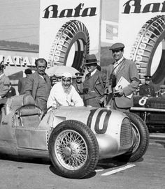 Hans Stuck in the Auto-Union racing car at the 1934 Brno Grand Prix at the Masaryk-Ring. Ferdinand Porsche is next to Hans Stuck on the left.
