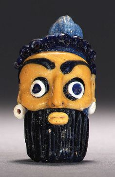 Phoenician glass head pendant, 5th-4th century B.C. Carthaginian rod formed of light blue glass with an opaque yellow face, with applied dark blue ringlets of hair along the forehead and a dark blue ribbed beard, the opaque yellow ears with opaque white blob earrings, the eyes dark blue on white on dark blue, with arching dark blue brows above, the mouth in opaque yellow, surmounted by a light blue suspension loop, 5.4 cm long. Private collection
