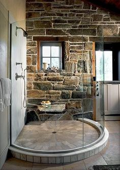 Invisible bath. This bathroom is so perfect that it's almost surreal. Curved glass for a circular walk-in glass shower surrounded by beautiful stonework and tilework.