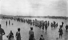 African porters were used in huge numbers during the East African campaign. A supply column carrying ammunition for the 2nd/4th Battalion, King's African Rifles is seen crossing the Lurio River during operations in Portuguese East Africa. Q 67823.