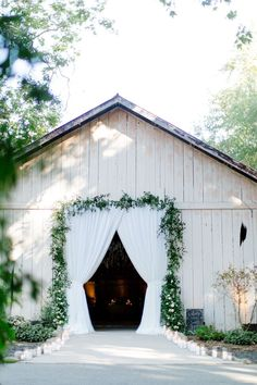 Rustic barn entrance transformed with white draping, romantic pillar candles, and smilax greenery framing the entrance.Elegant wedding at Dos Pueblos Ranch by Tyler Speier, with images by Christianne Taylor and Josh Newton. Monique Lhuillier bridal gown, flower wall, barn reception, elegant lighting, abundant organic white and green flowers, and hanging wisteria arrangements. Alabama Wedding Venues, Luxury Wedding Venues, Outdoor Wedding Venues, Wedding Decor, Wedding Ideas, Black Tie Wedding, Elegant Wedding, Indoor Wedding Ceremonies, Wedding Flower Inspiration