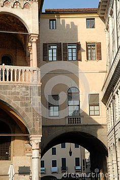 Photo made from the Piazza delle Erbe in the center of Padua in the Veneto (Italy). In the picture you see three different facades,  one in front belongs to a large two-story corridor that connects the ancient and important building that houses the Town Hall in the Palace of Reason of which you can see a small portion of the image to the left .