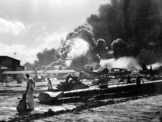 The Empire of Japan launched a surprise attack on the US naval base at Pearl Harbor in Hawaii on December 7, 1941, killing 2,350 people. In this photo, sailors stand amid wreckage watching as the USS Shaw explodes in the background. The attack effectively drew the United States into World War II.