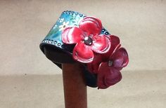 Hand tooled leather bracelet with red tooled leather flowers.