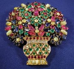 Gem-set and Diamond Flowerpot Brooch, composed of pear and circular-cut rubies, sapphires and emeralds interspersed with carved ruby leaves and oval cabochon cat's eye chrysoberyls, baguette and full-cut diamond highlights, 14kt gold mount.