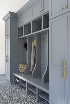 Well appointed blue mudroom boasts white and blue cement floor tiles accenting a blue bench fitted with shoe shelves and positioned against a blue shiplap trim finishing open lockers accented with brass hooks. lockers with bench Mudroom Cubbies, Mudroom Cabinets, Mudroom Laundry Room, Laundry Room Design, Mud Room Lockers, Shoe Storage Mudroom, Bench Mudroom, Entryway Storage, Armoire Entree