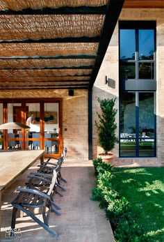 No pergolado, o forro de palha cobre o teto de vidro e traz uma atmosfera relaxante.