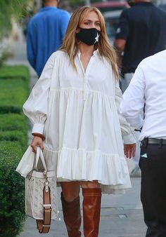 Jennifer Lopez in tiered white dress and knee high boots | For more style inspiration visit 40plusstyle.com
