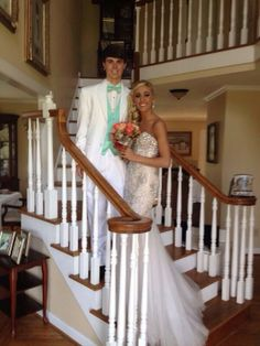 Adorable couple prom picture on the stairs. She's wearing an white prom dress from Mac Duggal with tons of sparkles and crystals.