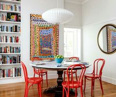 In love with this colour! Timber floorboards, grey-white walls, red Thonet chairs, Aboriginal art, marble-topped table, and books!