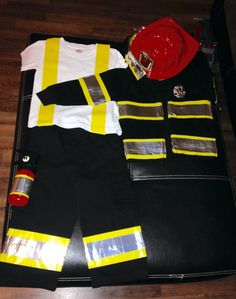 Rock's fireman costume was so simple and inexpensive to make this year! I spent $15 at Walmart on Black cargo pants, a black jacket, yellow duct tape, and silver duct tape. I also spent $5 at Burlington on a fireman tool kit full of accessories. I put yellow duct tape on an old white undershirt to mimic suspenders. This way he will still be in costume even if it is too hot for him to wear the fireman jacket. I ironed everything before I started taping.